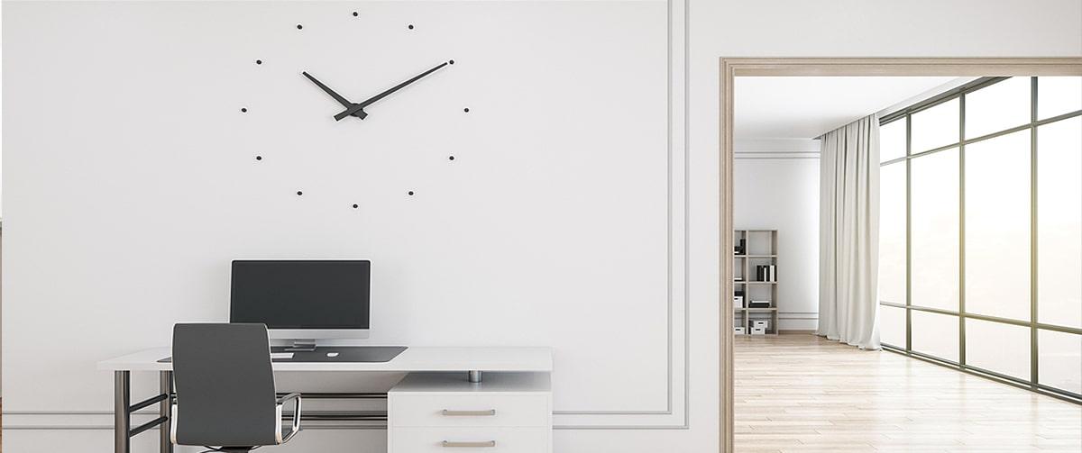 Grande horloge murale sous forme de stickers muraux au-dessus d'un bureau
