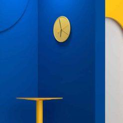 Horloge scandinave murale jaune sur un mur bleu