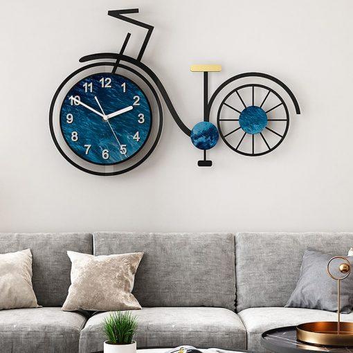 Horloge murale originale avec un grand vélo suspendue au-dessus d'un canapé